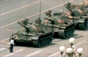 """Tank Man"" stops the advance of a column of tanks on June 5, 1989, in Beijing. This photograph, taken by Jeff Widener of the Associated Press, became one of the most famous images of the 20th century, and an international symbol at the end of the Cold War era."
