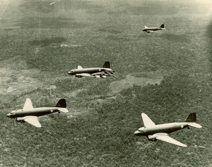 Four_C-47_escorted_by_P-40s_over_New_Guinea